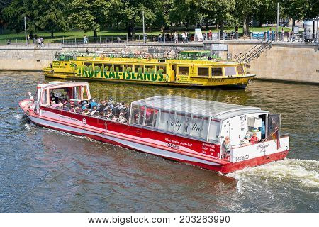 BERLIN, GERMANY - AUGUST 07, 2017: Excursion boats on the river Spree in Berlin. Many tourists take the opportunity to explore the city from the river