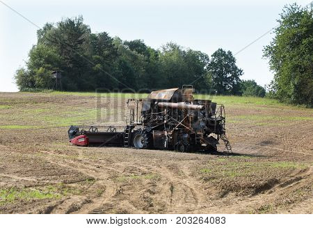 Burnt out combine harvester in field