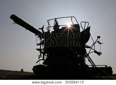 Silhouette of abandoned burnt out combine harvester in field at sunset