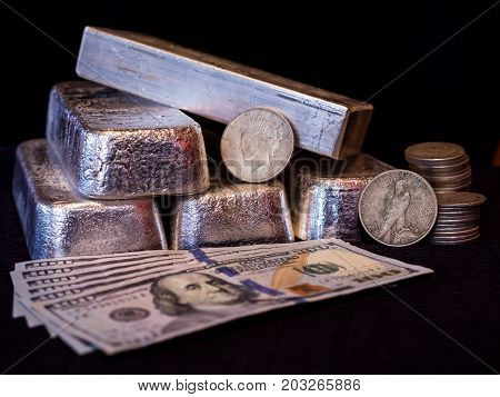 Multiple silver bars silver coins and paper currency displayed in front of a black background.