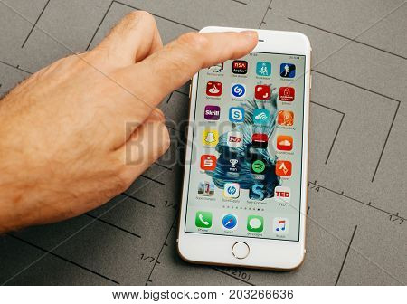 PARIS FRANCE - SEP 26 2016: Male hand holding New Apple iPhone 7 Plus after unboxing and testing by installing the app application software and selecting a random app from desktop