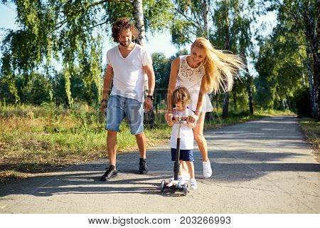 Happy family in the park. Parents with a child on a scooter are walking in nature.
