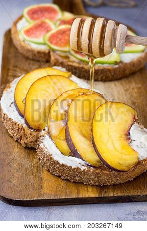 Pouring honey with wooden dipper on toast with whole grain bran rye bread slice with cream cheese peaches figs. Healthy snack dessert. Close up.