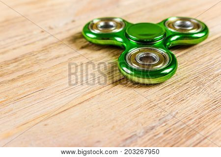 Spinner fidget toy for stress relieving on wood table background with copy space for your creative design project.