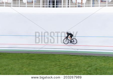 An active young man rides a bike on a velodrome. minimalist photo. sports topics. Cardio training.