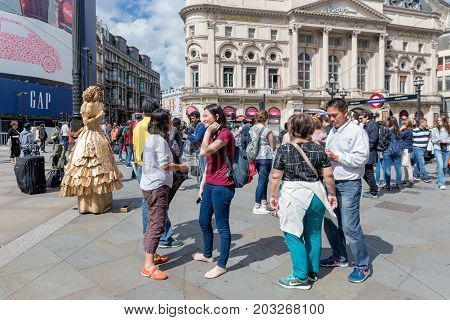 LONDON ENGLAND - JUNE 09 2017: Living statue and unknown people at Piccadilly Circus in London UK