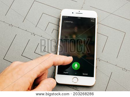 PARIS FRANCE - SEP 26 2016: Male hand holding New Apple iPhone 7 Plus after unboxing and testing by installing the app application software using Microsoft Translator with voice listening