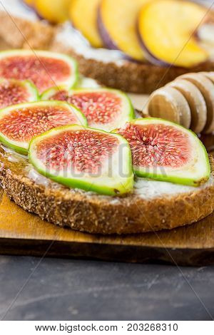 Toasts sandwiches with wholemeal rye bran bread cream cheese or yoghurt ripe figs and peaches. Wood honey dipper on cutting board. Close up.