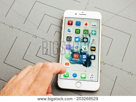 PARIS FRANCE - SEP 26 2016: Male hand holding New Apple iPhone 7 Plus after unboxing and testing by installing the app application software select Phone App
