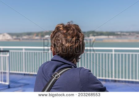 Woman at ferry leaving Dover looking backwards to the English coast