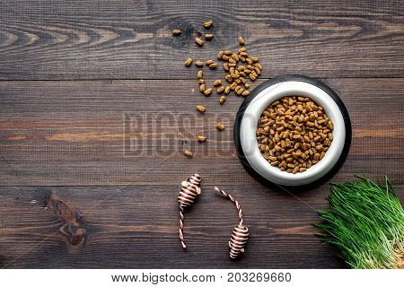 white plastic bowl full and overflowing with dry pet - cat food bits and mouse toys on wooden table background top view mock-up