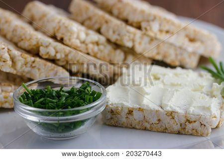 Rice cakes served with cream cheese and chives on white plate