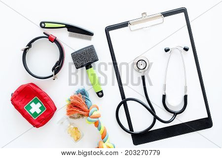 cure tools for pet cat and dog with toys, stethoscope for treatment in grooming set on white desk background top view
