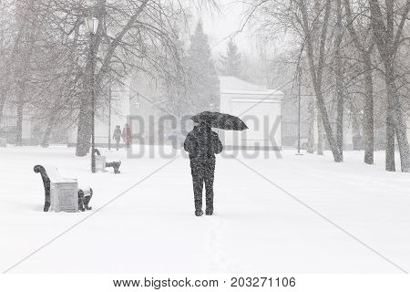 Bad weather in a city in winter: a heavy snowfall and blizzard. Male pedestrian hiding from the snow under umbrella