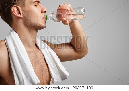 Side view of sporty fit man drinking water from bottle with eyes closed.