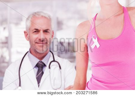 Mid section of woman wearing breast cancer awareness ribbon against portrait of doctor standing with arms crossed