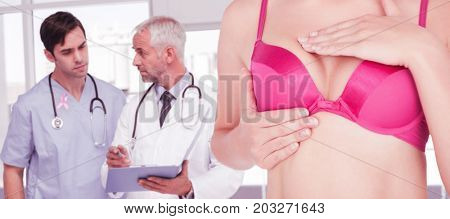 Mid section of woman in pink bra checking breast for cancer awareness against doctors talking about a file