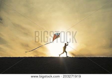 boy running with a kite on sunset background. silhouette of child playing with kite. Copy space for your text