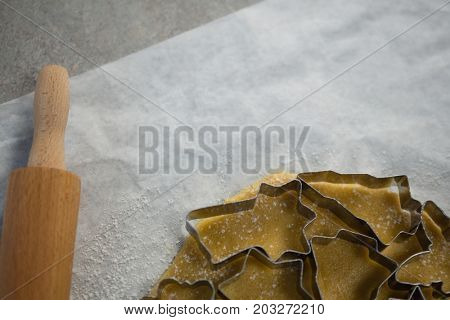 Cropped image of various pastry cutters over dough on wax paper at table