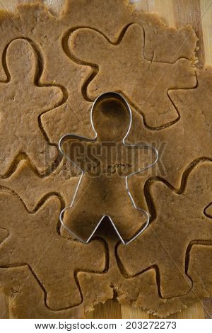 Gingerbread man pastry cutter on dough over cutting board