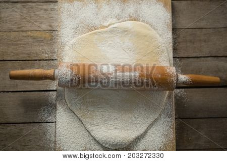 Overhead view of rolling pin on rolled dough over cutting board at table
