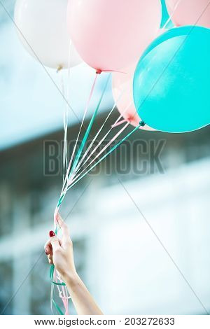 female hand holds flying multicolored latex balloons
