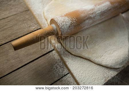 High angle view of rolling pin on rolled dough over cutting board at table