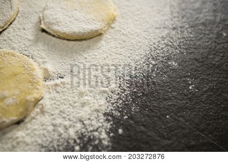 Cropped image of flour on unbaked cookies on table