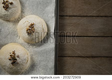 Directly above shot of unbaked cookies with cardamom on baking sheet at table