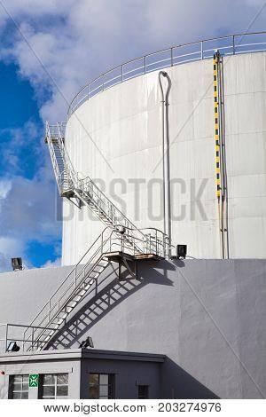 White tanks in tank farm with iron staircase