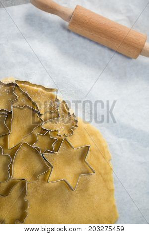 Close up of various shape pastry cutter on rolled dough on wax paper