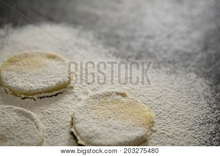 Close up of flour on unbaked cookies on table
