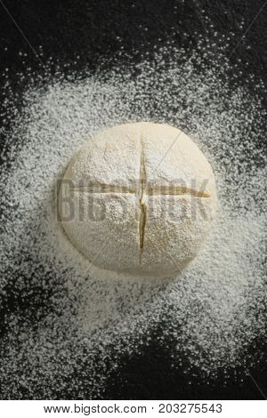 Overhead view of flour on unbaked bun at table
