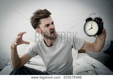 Portrait Upset Angry Young Man Screaming At Alarm Clock On Bedroom. Employee Running Late. Time Mana