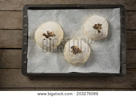 Overhead view of unbaked cookies with cardamom on baking sheet at table
