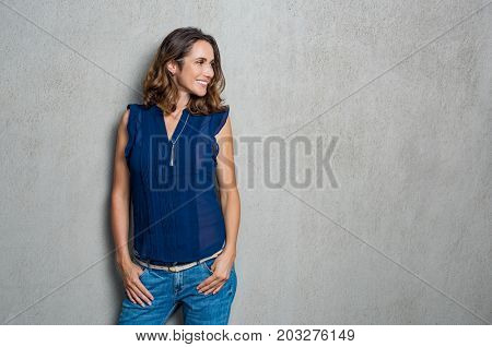 Happy smiling woman dressed in a blue dress isolated on grey background. Mature woman looking away against grey background. Beautiful woman in casual thinking with copy space.
