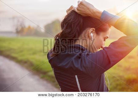 Woman tying hair in ponytail getting ready for exercising at sunset. Beautiful young sporty woman attaching her long hair in park. Smiling woman tightening hair for jogging at park.