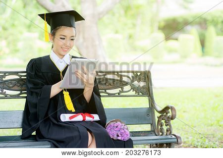 Graduate Playing Tablet In Her Hand Feeling Relaxing And So Happiness In Commencement Day And Search