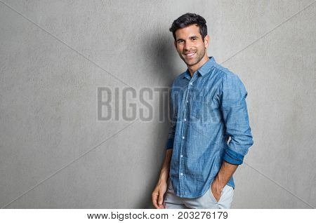 Happy smiling man leaning against grey wall. Portrait of proud mid man isolated on grey background. Young casual hispanic man against grey wall looking at camera.