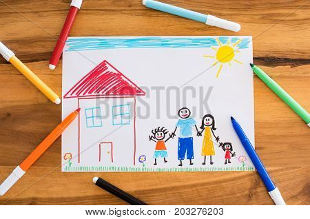 Top view of colored drawing of happy family holding hands together. Little child painted his family on paper. High angle view of painting and markers on table. Concept of unity and love.