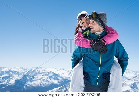 Young couple having fun on snow. Happy man at the mountain giving piggyback ride to his smiling girlfriend. Cheerful boyfriend holding loving woman on his back with copy space.