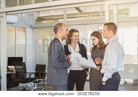 Company employees in conversation regarding paperwork in meeting room. Manager and businessman with businesswomen working together in modern office. Conversation with colleagues in modern office.