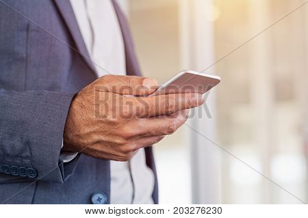 Close up of a man using mobile smart phone. Close up hand of businessman in formals typing on smartphone. Detail of businessman holding cellphone while checking emails.