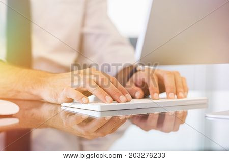Closeup of businessman hands typing on modern computer keyboard. Detail of man's hand on computer keyboard writing an email. Man working on computer at modern desktop.