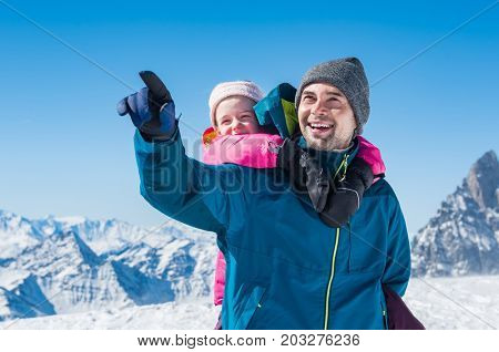 Young father enjoying with daughter a sunny winter day. Happy father with daughter enjoying winter vacation over mountains. Cheerful father giving piggyback ride to daughter while pointing mountain.