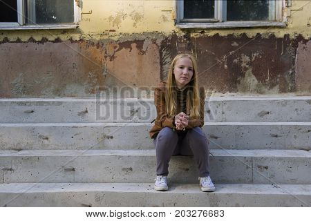 Sad teenage girl sitting on stairs steps