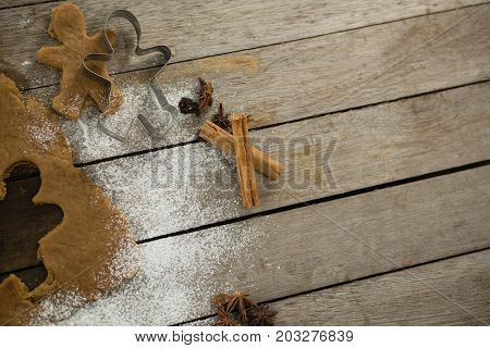 Overhead view of dough with pastry cutter on wooden table