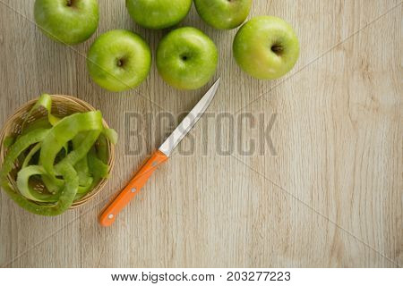 Overhead view of granny smith apples by peel in basket on table
