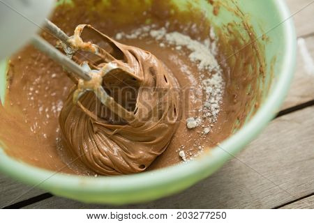 Overhead view of electric mixer mixing flour and chocolate batter in bowl on table