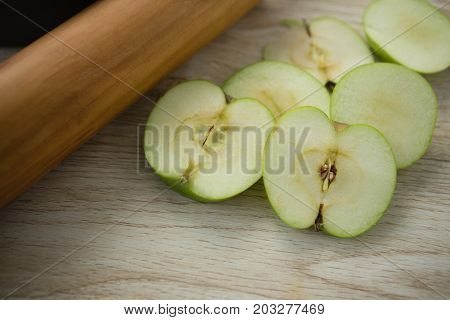High angle view of granny smith apple slices by rolling pin on wooden table